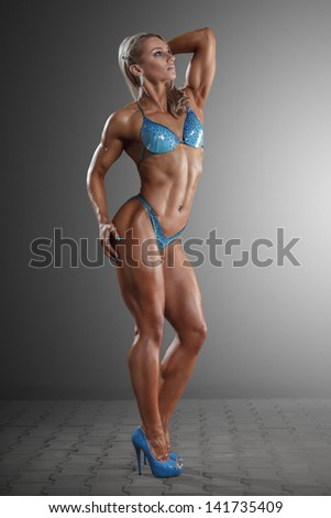 Athletic young woman posing against dark studio background - stock photo