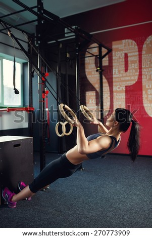 Athletic young woman practicing on the rings in the gym. Back view, muscular woman Caucasian appearance, brunette, is engaged in the gym - stock photo