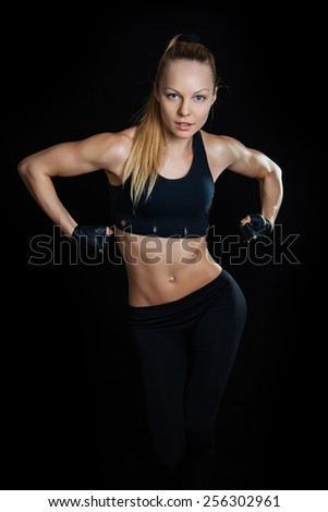 Athletic young woman showing muscles arms on a isolated black background - stock photo