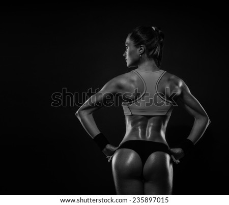 Athletic young woman showing muscles of the back and hands on a isolated black background - stock photo