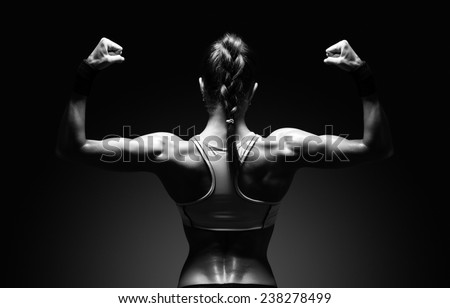 Athletic young woman showing muscles of the back and hands on a isolated black background with clipping path - stock photo