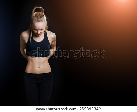 Athletic young woman showing trained beautiful body and pumped abdominals  - stock photo
