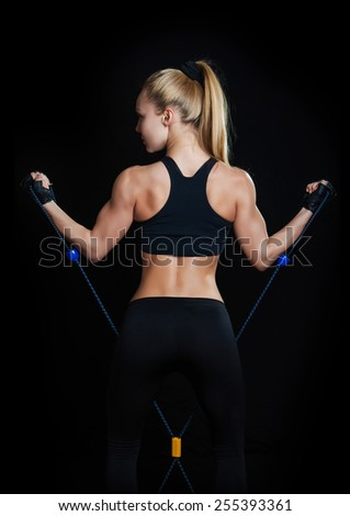 Athletic young woman working on biceps with expander - stock photo
