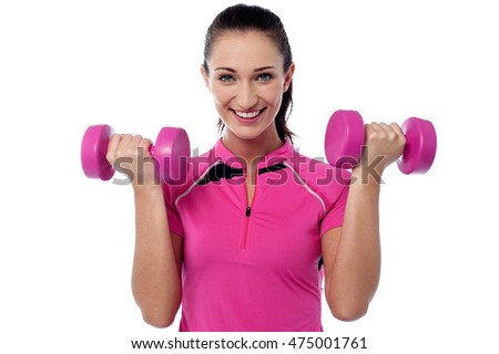 Athletic young woman works out with pink dumbbells.