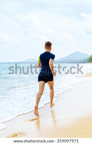 Athletics. Fit Athlete Male Jogger Running On Beach. Athletic Sporty Man Jogging On Wet Sand During Workout Outside. Sports, Run, Fitness And Exercising. Healthy Lifestyle, Wellness And Health Concept