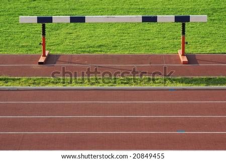 athletics hurdle on stadium and red running tracks - stock photo