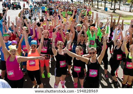 ATLANTA, GA - APRIL 5:  A throng of excited runners gathered at start line, jubilantly waves to camera at the Ridiculous Obstacle Challenge (ROC) 5k race, on April 5, 2014 in Atlanta, GA.   - stock photo