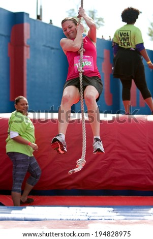 ATLANTA, GA - APRIL 5:  A young woman holds on and swings with a rope in one of the events at the Ridiculous Obstacle Challenge (ROC) 5K race, on April 5, 2014 in Atlanta, GA.  - stock photo