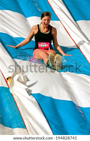 ATLANTA, GA - APRIL 5:  A young woman screams with delight while sliding down a watery plastic slide in the Ridiculous Obstacle Challenge (ROC) 5K race, on April 5, 2014 in Atlanta, GA.  - stock photo