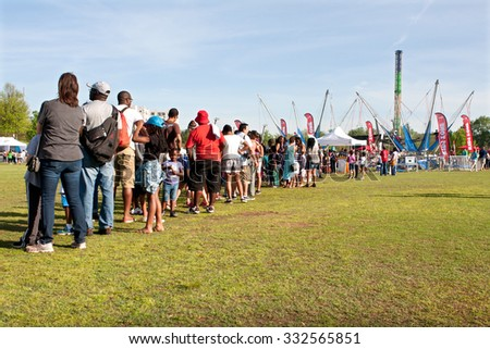 ATLANTA, GA - APRIL 11:  Parents and kids stand in a very long line waiting their turn for the bungee jump ride at the Atlanta Dogwood Festival in Piedmont Park on April 11, 2015 in Atlanta, GA.  - stock photo