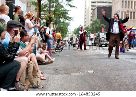 ATLANTA, GA - AUGUST 31:  A huge crowd of spectators lines Peachtree Street in downtown Atlanta, and takes pictures as the annual Dragon Con parade passes by on August 31, 2013 in Atlanta, GA.  - stock photo