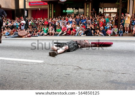ATLANTA, GA - AUGUST 31:  A man plays dead after a medieval fight scene in front of spectators watching the Dragon Con parade on Peachtree Street, on August 31, 2013 in Atlanta, GA .   - stock photo