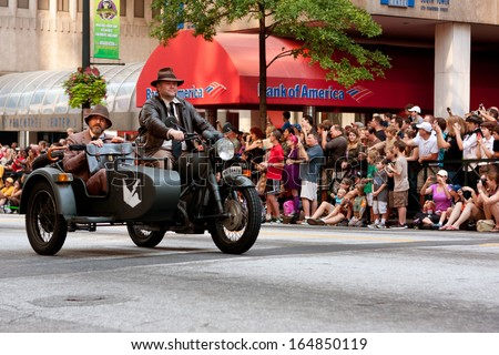 ATLANTA, GA - AUGUST 31:  Two men dressed like characters from the Indiana Jones movies, ride a motorcycle down Peachtree Street in the annual Dragon Con parade on August 31, 2013 in Atlanta, GA.  - stock photo