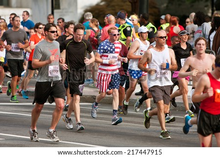 ATLANTA, GA - JULY 4:  A runner dressed in stars and stripes from head to toe, runs toward the finish line of of the Peachtree Road Race on Independence Day, on July 4, 2014 in Atlanta, GA.   - stock photo
