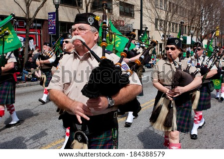 ATLANTA, GA - MARCH 15:  A bagpipes corps plays the bagpipes while marching in the St. Patrick's parade on Peachtree Street, on March 15, 2014 in Atlanta, GA.  - stock photo