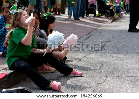 ATLANTA, GA - MARCH 15:  Kids eat cotton candy while watching the annual St. Patrick's parade pass by on Peachtree Street, on March 15, 2014 in Atlanta, GA.  - stock photo