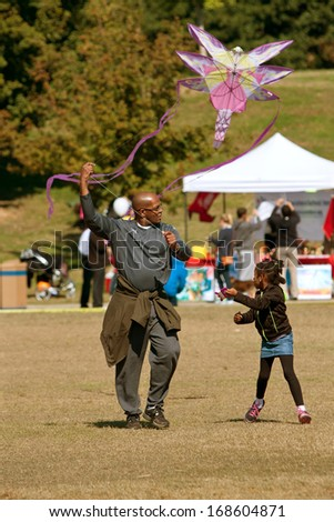 ATLANTA, GA - OCTOBER 26:  A father and daughter try to get their kite to take flight, at the World Kite Festival at Piedmont Park on October 26, 2013 in Atlanta, GA.  The event was free.   - stock photo