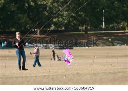 ATLANTA, GA - OCTOBER 26:  A woman gets her kite airborne at the World Kite Festival in Piedmont Park, on October 26, 2013 in Atlanta, GA.  The event was free to the public.  - stock photo