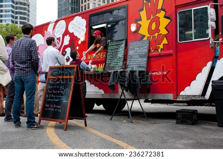 "ATLANTA, GA - OCTOBER 16:  Customers wait in line to order meals from a popular food truck during their lunch hour, at ""Food Truck Thursday"" on October 16, 2014 in Atlanta. - stock photo"