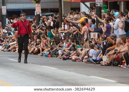ATLANTA, GA - SEPTEMBER 5:  A man dressed like a Star Trek character waves to a huge throng of spectators as he walks in the annual Dragon Con Parade on September 5, 2015 in Atlanta, GA.  - stock photo