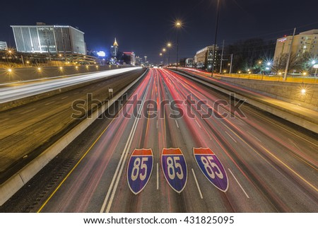 Atlanta, Georgia, USA - February 15, 2014:  Interstate highway 85 pavement signs, downtown skyline and traffic at night. - stock photo