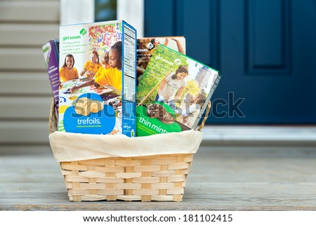 ATLANTA - MARCH 9, 2014: Assortment of packaged Girl Scout cookies in basket delivered on front porch.  - stock photo