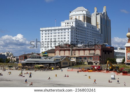 Atlantic City, New Jersey, USA - Aug 24, 2014: Tourist enjoying the beach in front of the Resorts Casinos with Jimmy Buffett's Margaritaville restaurant in Atlantic City, New Jersey. on Aug 24, 2014 - stock photo