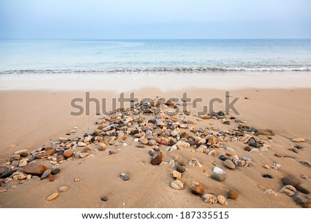 Atlantic ocean coast with wet small stones on the sand - stock photo