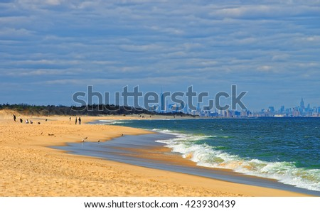Atlantic Ocean shore at Sandy Hook with view of NYC. Sandy Hook is in New Jersey, USA. Tourists on the shore - stock photo