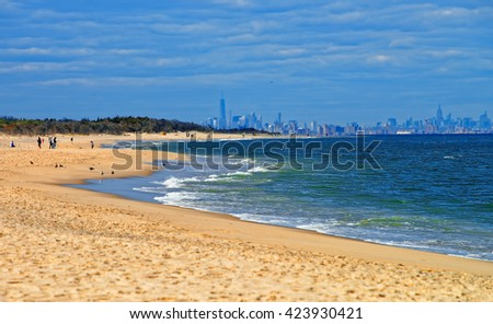 Atlantic Ocean shore at Sandy Hook with view on NYC. Sandy Hook is in New Jersey, USA. Tourists on the shore - stock photo