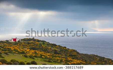 Atlantic Ocean. Summer coastal landscape of Gibraltar strait, Morocco. Small living house with national flag stands on the coast - stock photo