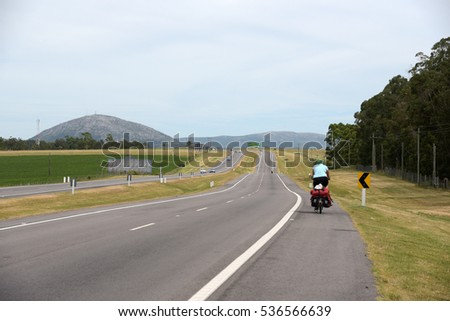 ATLANTIDA, URUGUAY, JANUARY 20: Female cyclist riding in main road 18 to a tourist village on January 20,2016.Atlantida is a mayor destination for Argentinian tourist during summer time