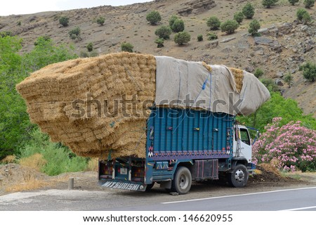 ATLAS, MOROCCO - JULY 10: Overloaded truck staying on road, July 10, 2013 in Atlas Mountains, Morocco. Road in Atlas Mountains very popular tourist route in central Morocco. - stock photo