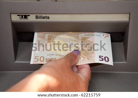 ATM Access : a womans hand withdraws money at cashpoints - stock photo