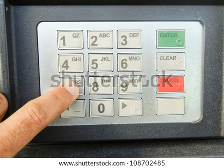 ATM Keypad with a person entering passcode or ATM pin number
