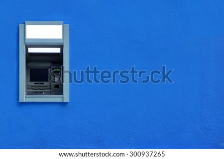ATM Or ABM Or Cashpoint Machine Or Hole In The Wall Byilt-In The Blue Concrete Wall Textured Background With Copy Space - stock photo