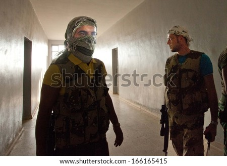 ATME, SYRIA -  JUNE  18, 2012 - Unidentified rebels of the Free Syrian Army in rebel controlled building on June 18, 2012 in Atme, Syria. Atme is just across the Turkish border  - stock photo