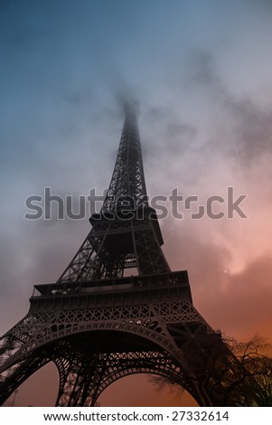 Atmospheric capture of Eiffel Tower with fog rolling in as the Sun sets. Taken with a wide angle Lens in early March - stock photo