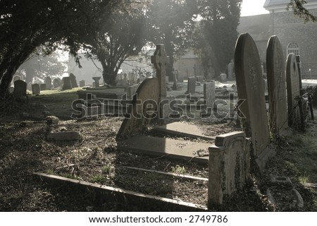Atmospheric cemetery scene in contre jour, taken early on a frosty morning - stock photo