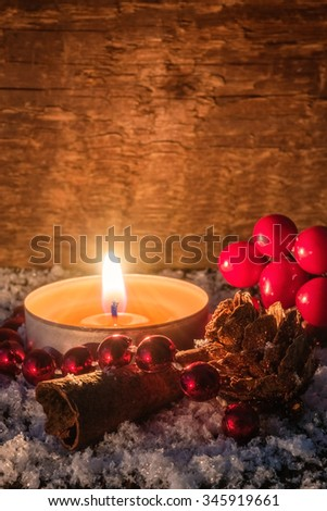 Atmospheric christmas card or background with burning tea light, candle,cinnamon, pine cone and cranberries on a wooden table covered with snow. Greeting card. Selected focus, narrow depth of field. - stock photo