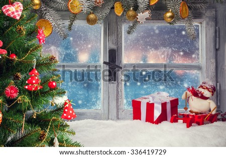 Atmospheric Christmas window sill decoration with beautiful sunset view.Christmas tree on foreground - stock photo
