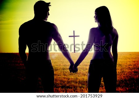 Atmospheric conceptual image of the silhouettes of a romantic young couple holding hands standing with their backs to the camera in a field with a cross visible beyond them - stock photo