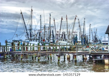 Atmospheric HDR image of a fishing fleet in the harbor in the early morning light.  All boat names removed.   - stock photo