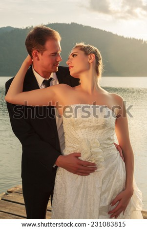 Atmospheric image of a newlywed bride and groom in embrace standing on a lake at sunset. / Atmospheric image of a newlywed newlyweds - stock photo