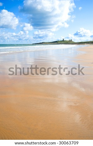 Atmospheric low and wide angle shot of tidal rivulets on Embleton beach with Dunstanburgh castle in the background - stock photo