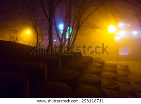 Atmospheric night foggy city park illuminated by street lights (diffused, toned). Blurred dreamy cityscape. - stock photo