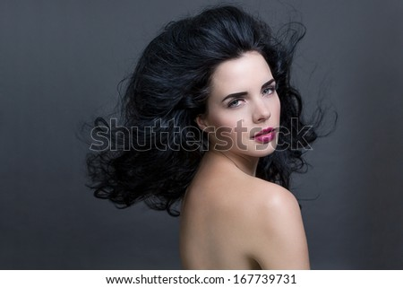 Atmospheric studio portrait of a beautiful black haired woman with a gentle serene expression gazing over her naked shoulder directly at the camera, close up head and shoulders against black