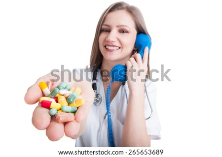 Atractive and young woman doctor talking on the phone and offering pills - stock photo