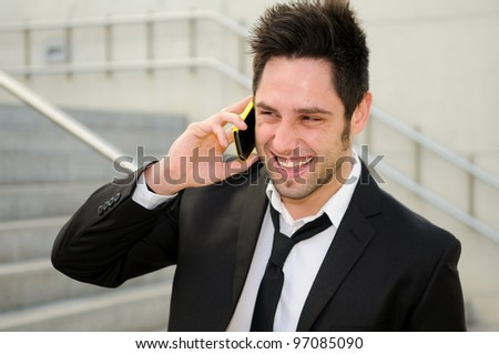 Atractive man in urban background talking on phone - stock photo