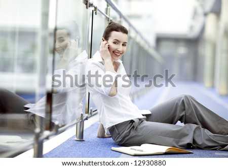 Atractive young woman sitting on the floor in modern office building corridor with mobile phone in her hand - stock photo